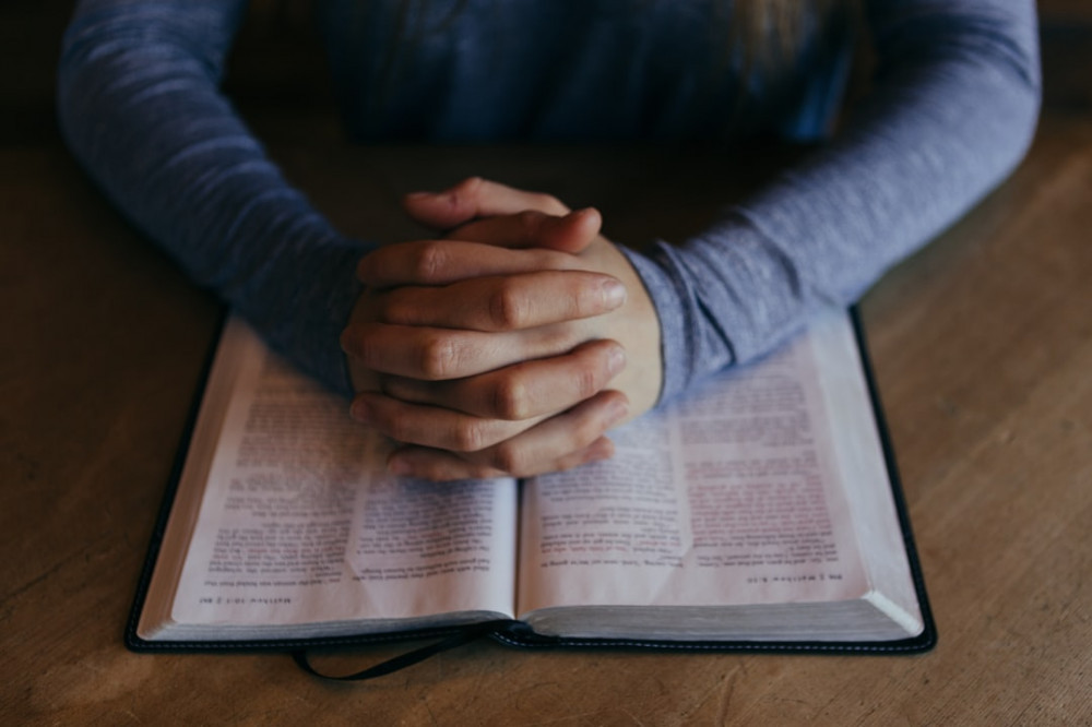 Christian Praying with Folded Hands and Opened Bible