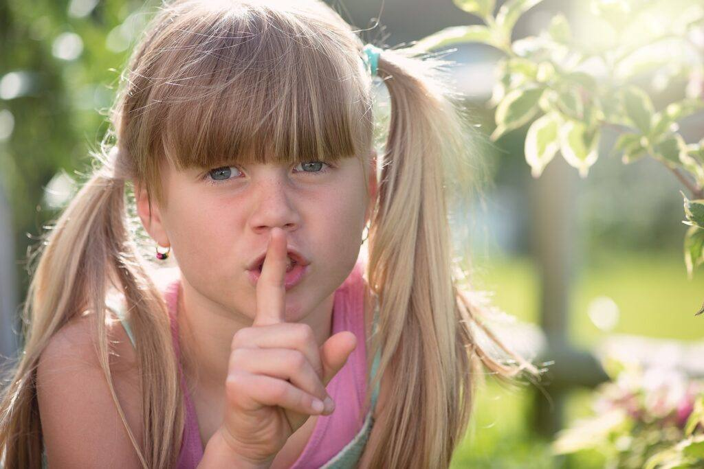 Girl Holds Finger to Nose Be Quiet