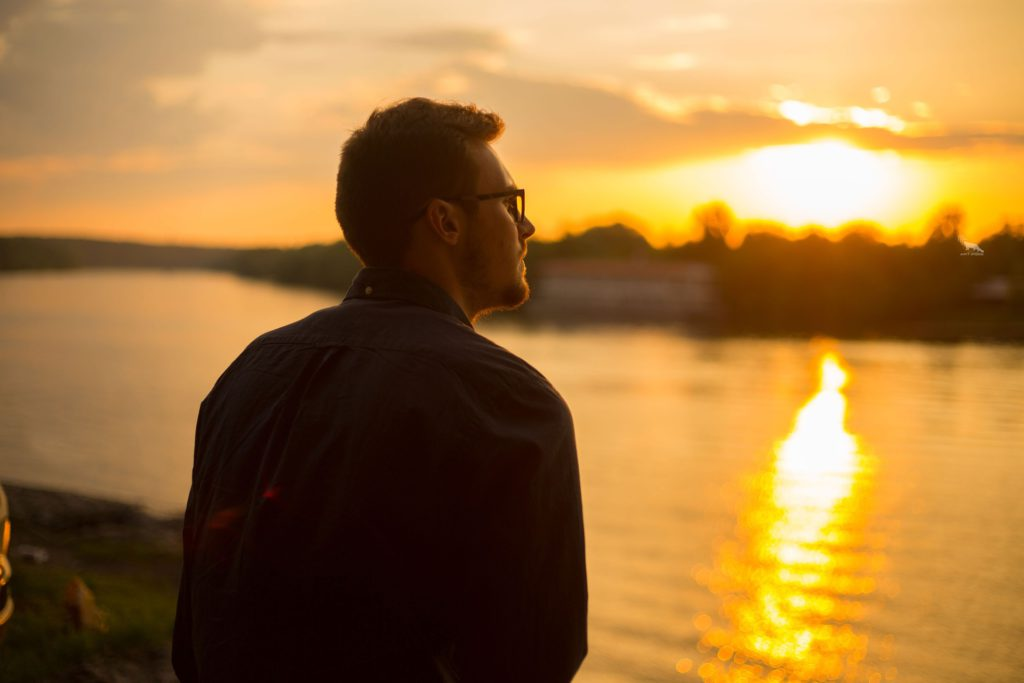 Guy Sitting by River Facing Sunset