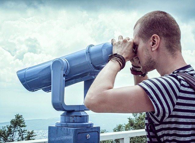 Man Looks Through Sightseeing Binocular