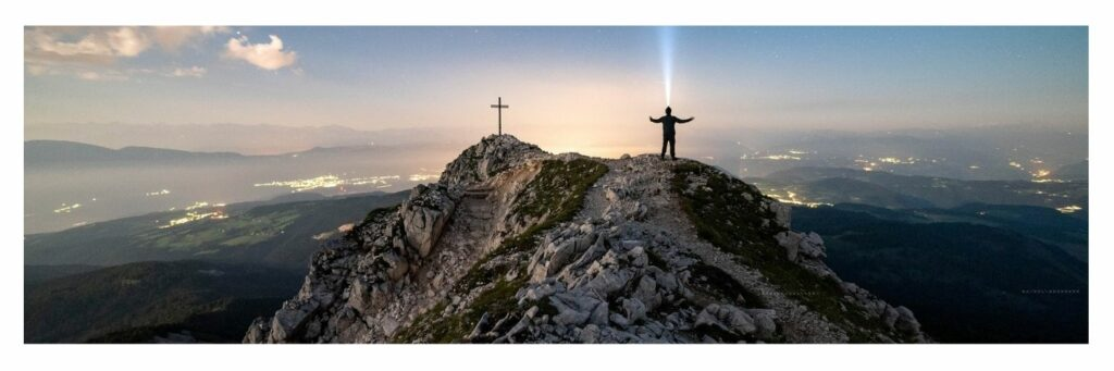 Man Standing on the Mountain Facing the Cross