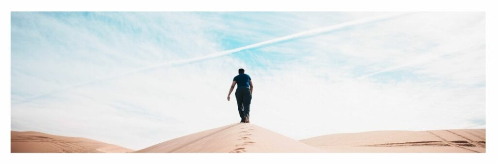 Man Walking in the Middle of Desert with Blue Sky