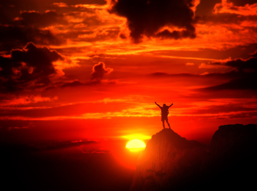 Man on Top of the Mountain with Raised Arms