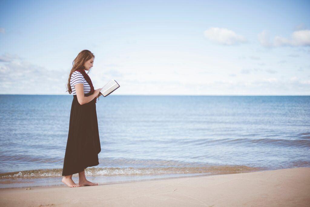 Woman Reading Bible by Sea